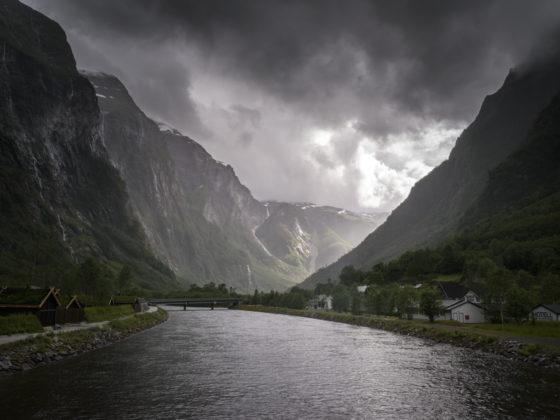 Donker wolken pakken zich samen, toch schijnt de zon achter de bergen. De zon staat voor de kansen en mogelijkheden in deze moeilijke tijd.